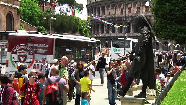 Tourists stop to watch a street performer being Cola di Rienzo near Rome's Coliseum. Freeze frame of video shot by AP cameraman Pietro De Cristofaro. June 2013