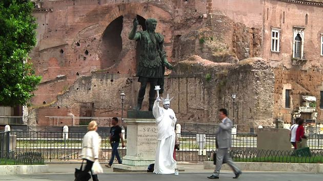 A street performer imitates the State of Liberty in front of a statue of Julius Caesar in Rome. Freeze frame of video shot by AP cameraman Pietro De Cristofaro in Rome. June 2013