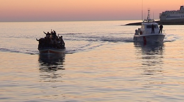 A boat of immigrants being escorted by the Coast Guard into the port of Lampedusa.  Freeze frame of video shot by AP cameraman Paolo Lucariello April 4, 2011