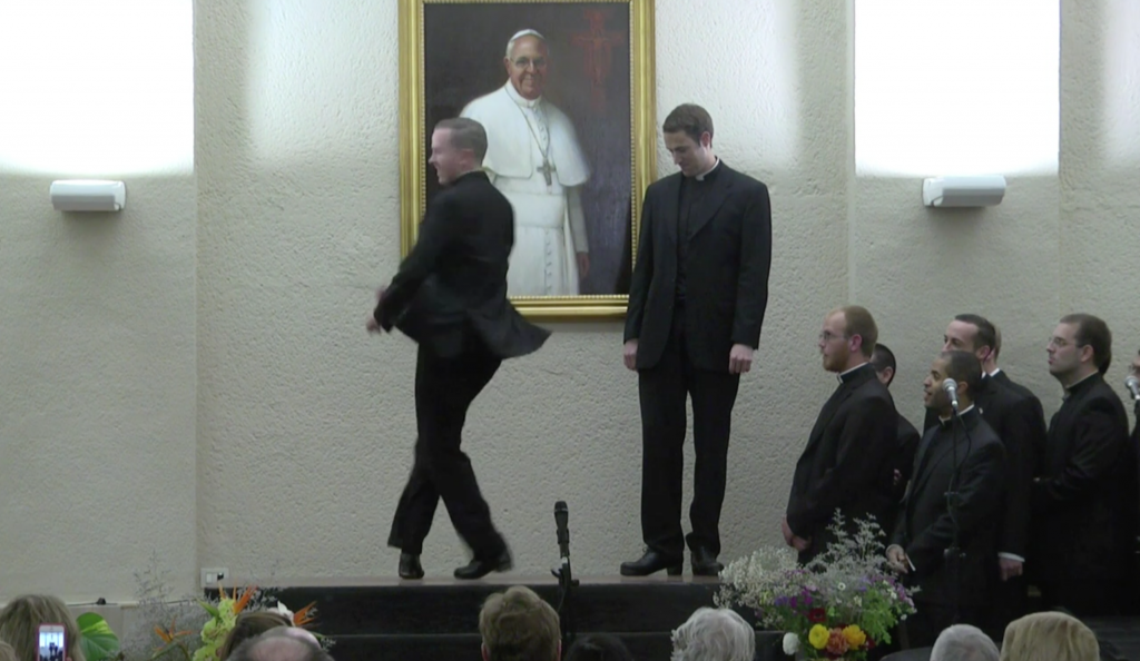 Father David Rider spinning around in a dance routine at the North American College performance. April 29, 2014. Freeze frame of Video. Credit: Pontifical North American College and Mr. J William Sumner