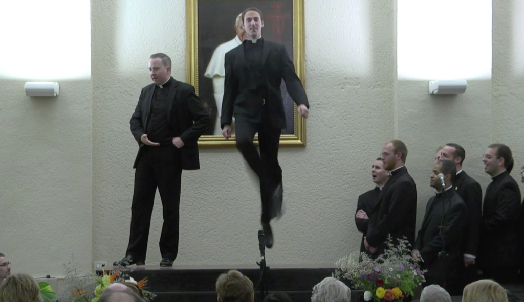 Father John Gibson jumping high in an Irish dance routine at the North American College performance. April 29, 2014. Freeze frame of Video. Credit: Pontifical North American College and Mr. J William Sumner