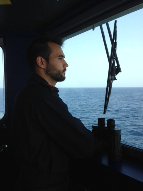 Portuguese sailor aboard the Viana Do Castelo looks out towards the sea for migrants as his ship sails south of the Italian island of Lampedusa. November 12, 2014. Photo by Trisha Thomas
