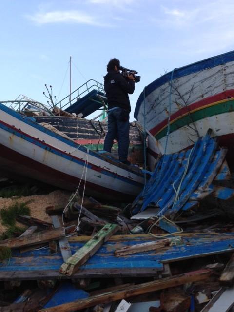 Associated Press video-journalist Paolo Santalucia filming the boat graveyard on the Italian island of Lampedusa. November 11, 2014. Photo by Trisha Thomas