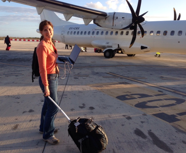 Trisha Thomas heading for the plane on the runway in Lampedusa, macbook in one hand, computer bag in the other. Photo by Paolo Santalucia. November 13, 2014