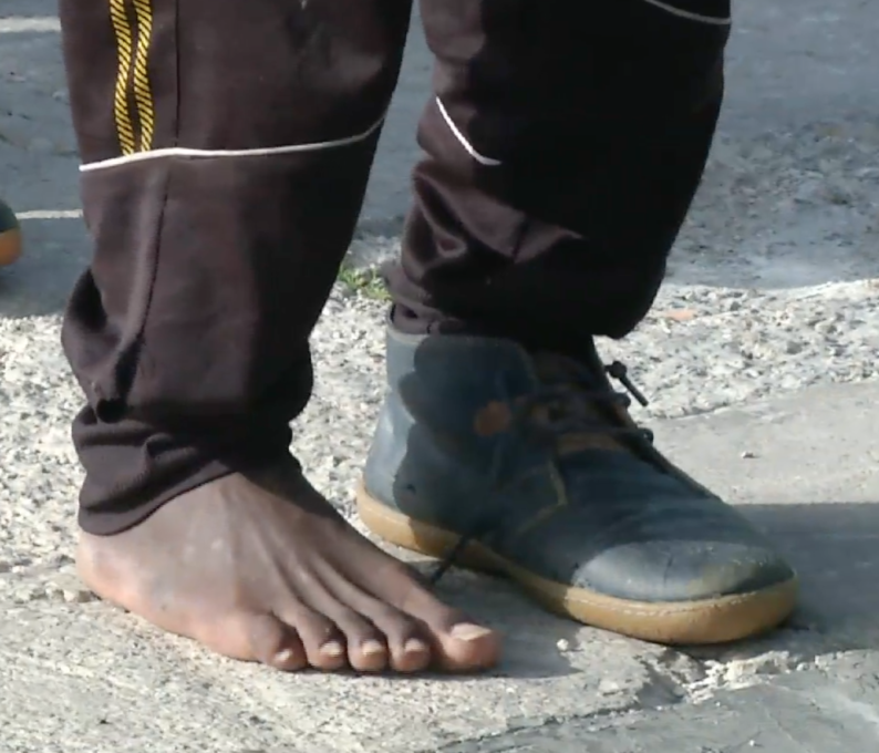 A migrant rescued at sea disembarks from a Coast Guard ship in the Italian port of Pozzallo with one shoe and one bare foot.  April 17, 2015. Freeze frame of video shot by AP Television Cameraman Luigi Navarra
