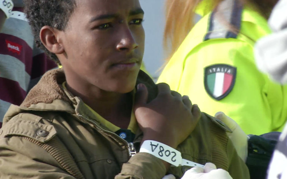 A young migrant with a number, 208A, looks determined and hopeful as he stands in the port of Pozzallo, Sicily after being rescued at sea.  Freeze frame of video shot by AP Television Cameraman Luigi Navarra April 17, 2015