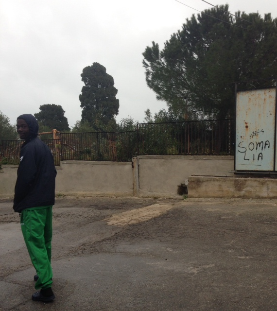 """A migrant turns back to look at me curiously as I take his picture as he walks past some graffiti with the word """"Somalia"""" outside the """"Umberto I"""" migrant holding center near Siracusa, Sicily. March 24, 2015. Photo by Trisha Thomas"""
