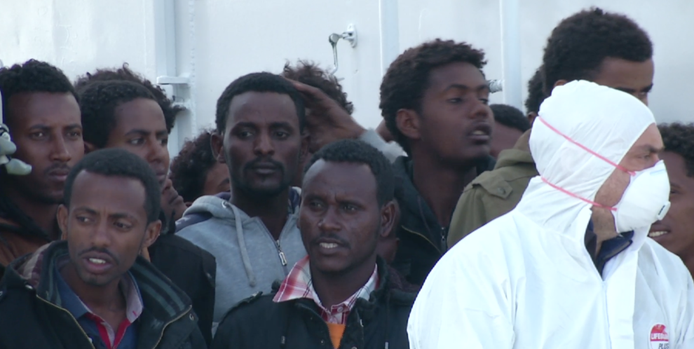 Migrants packed on the deck of a Coast Guard ship as it docks in port eagerly looking towards the shore.  Freeze frame of video shot by AP Television Cameraman Luigi Navarra, April 17, 2015