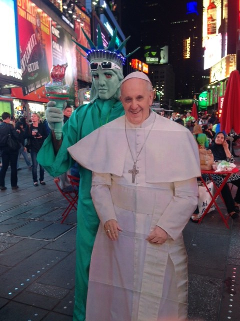 A cardboard cut-out of Pope Francis being held up by the Statue of Liberty in Times Square, New York. September 25, 2015. Photo by Trisha Thomas