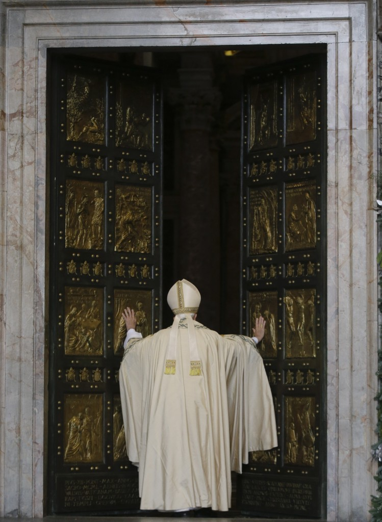 Pope Francis pushes open the Holy Door on St. Peter's Basilica. December 8, 2015. Photo by AP Photographer Gregorio Borgia