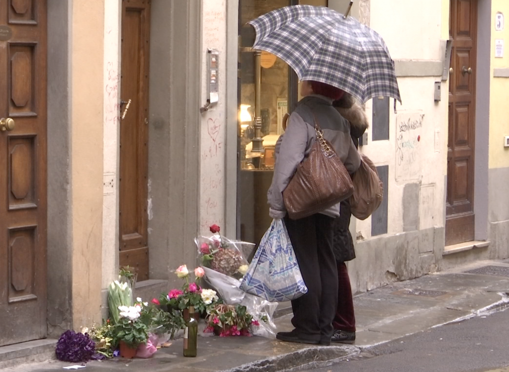 Passersby read messages left by friends of Ashley Olsen outside her apartment in Florence. Freeze frame of video shot by AP Cameraman Gigi Navarra for Associated Press Television. January 14, 2016