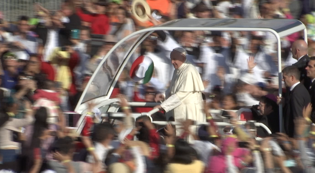 A woman waves a tri-color Mexican hat as Pope Francis arrives at the Basilica of Our Lady of Gaudalupe. Freeze frame of video by AP VJ Paolo Santalucia. February 13, 2016