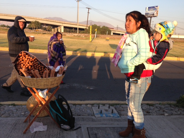 Rosa with her baby Jesus on her back selling Churros to people arriving at Mass in Ecatepec. February 14, 2016. Photo by Trisha Thomas
