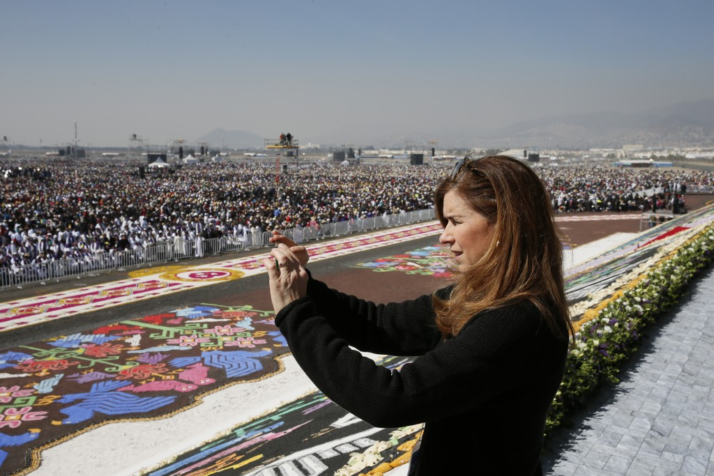 Trisha Thomas taking a picture of crowd at Papal Mass in Ecatepec, Mexico. Photo by Paul Haring of Catholic News Service. February 14, 2016