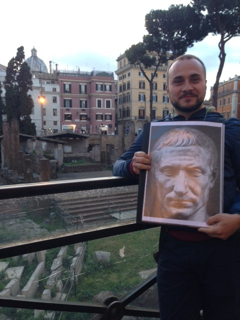 Massimo De Filippis showing a photo of a statue of Julius Caesar at Piazza di Torre Argentina in Rome. May 2016