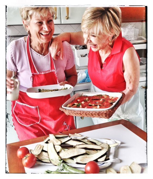 Katherine Wilson's mother-in-lawe working on a Parmiginana di Melanzane (Eggplant Parmesan) dish with her sister. Credit: Tara Crossley